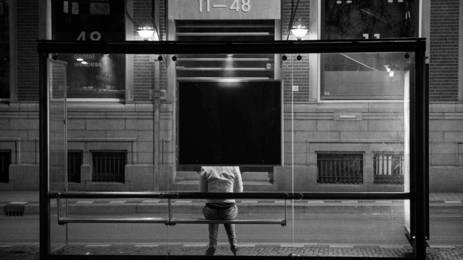 Foto: Una mujer espera el autobús sentada en una marquesina.