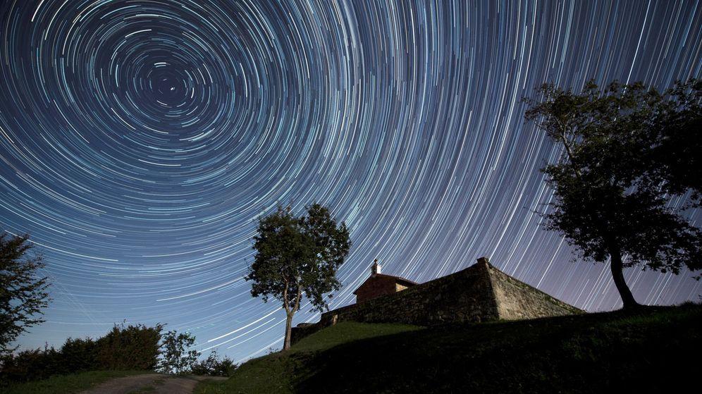 Foto: Imagen de larga exposición que muestra las estrellas circumpolares sobre la ermita de San Esteban, en Comillas, Cantabria. (EFE)