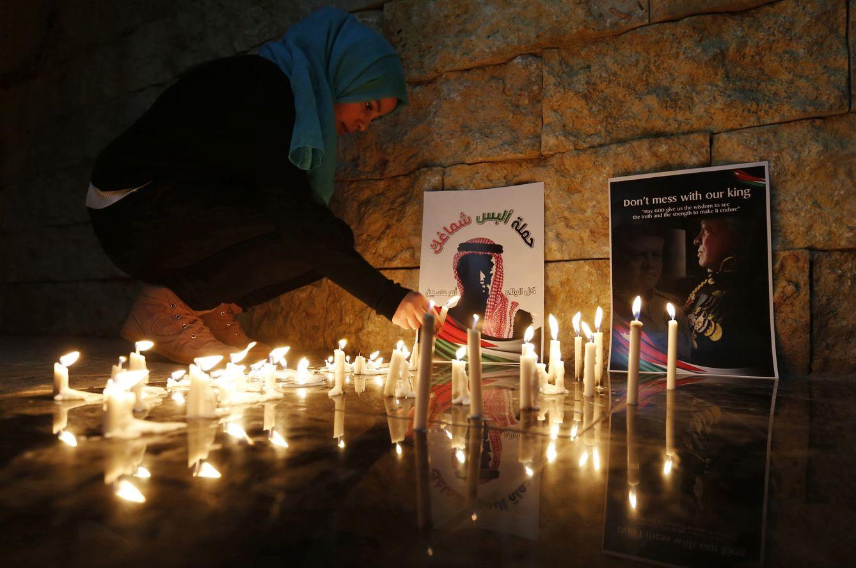 Foto: Una jordana enciende una velas cerca de una foto del piloto jordano ejecutado por el ISIS, Muath al-Kasasbeh, en Amman. (Reuters)
