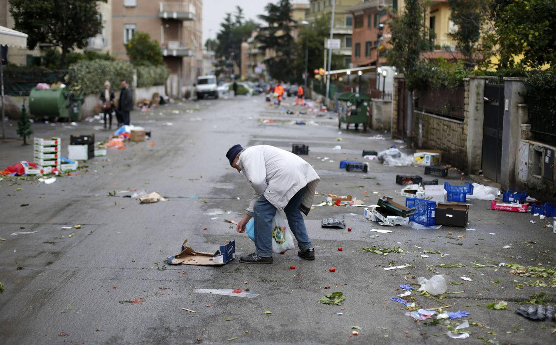 Foto: Un hombre recoge comida del suelo tras un mercado callejero en Roma, en diciembre de 2012 (Reuters).