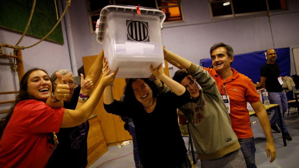 Foto: Los voluntarios levantan en señal de victoria una urna en el cierre de la votación. (Reuters)