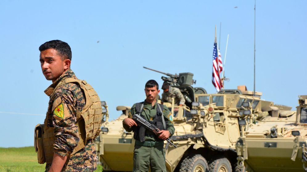 Foto: Milicianos kurdos montan guardia junto a un blindado estadounidense en la localidad siria de Ghanamya, cerca de la frontera con Turquía, en abril de 2017. (EFE)