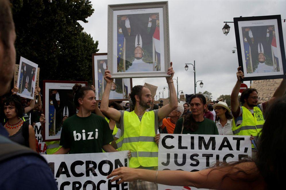 Foto: Protestas contra la cumbre del G-7 en Baiona con una manifestación con los retratos oficiales de Macron boca abajo. (EFE)