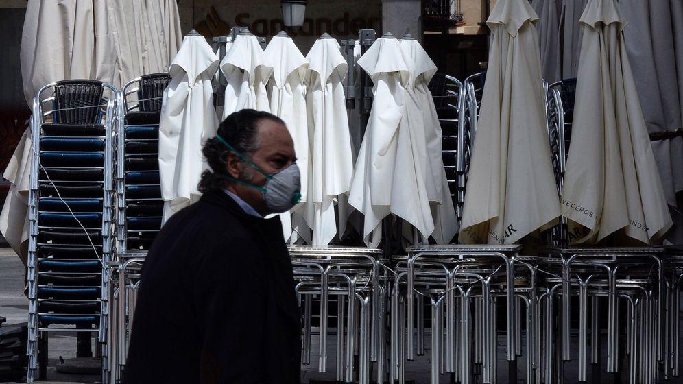 Foto: Un hombre ataviado con una mascarilla pasa por delante de una terraza recogida de un bar de Valladolid. (EFE)