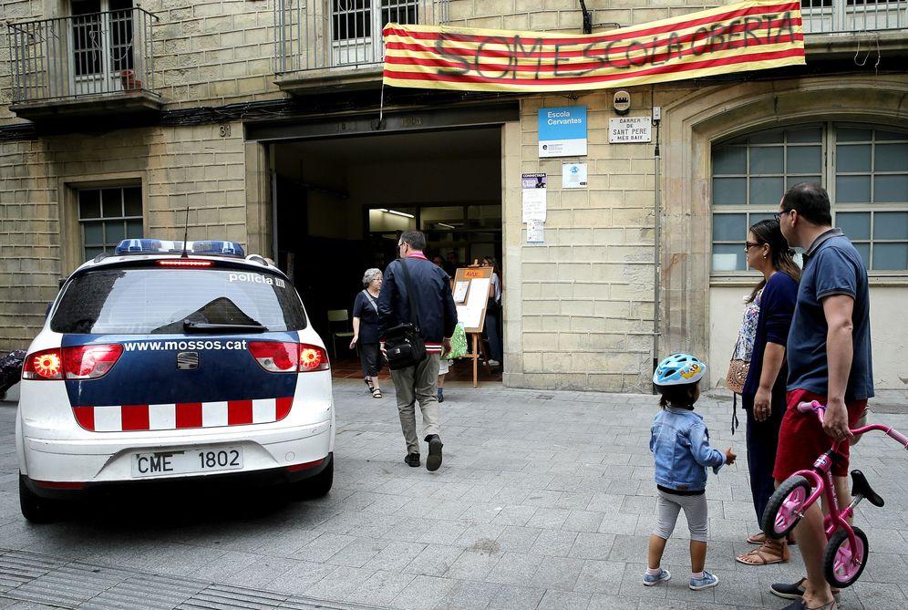 Foto: Una familia contempla la llegada de los Mossos al colegio Cervantes de Barcelona. (EFE)
