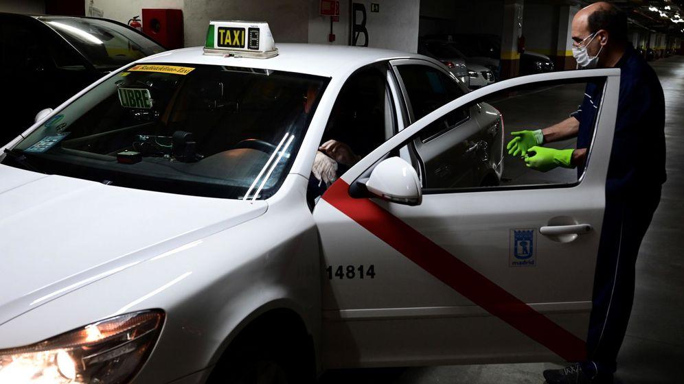 Foto: Un taxista efectúa las medidas de limpieza y protección en su vehículo. (Víctor Lerena, EFE)