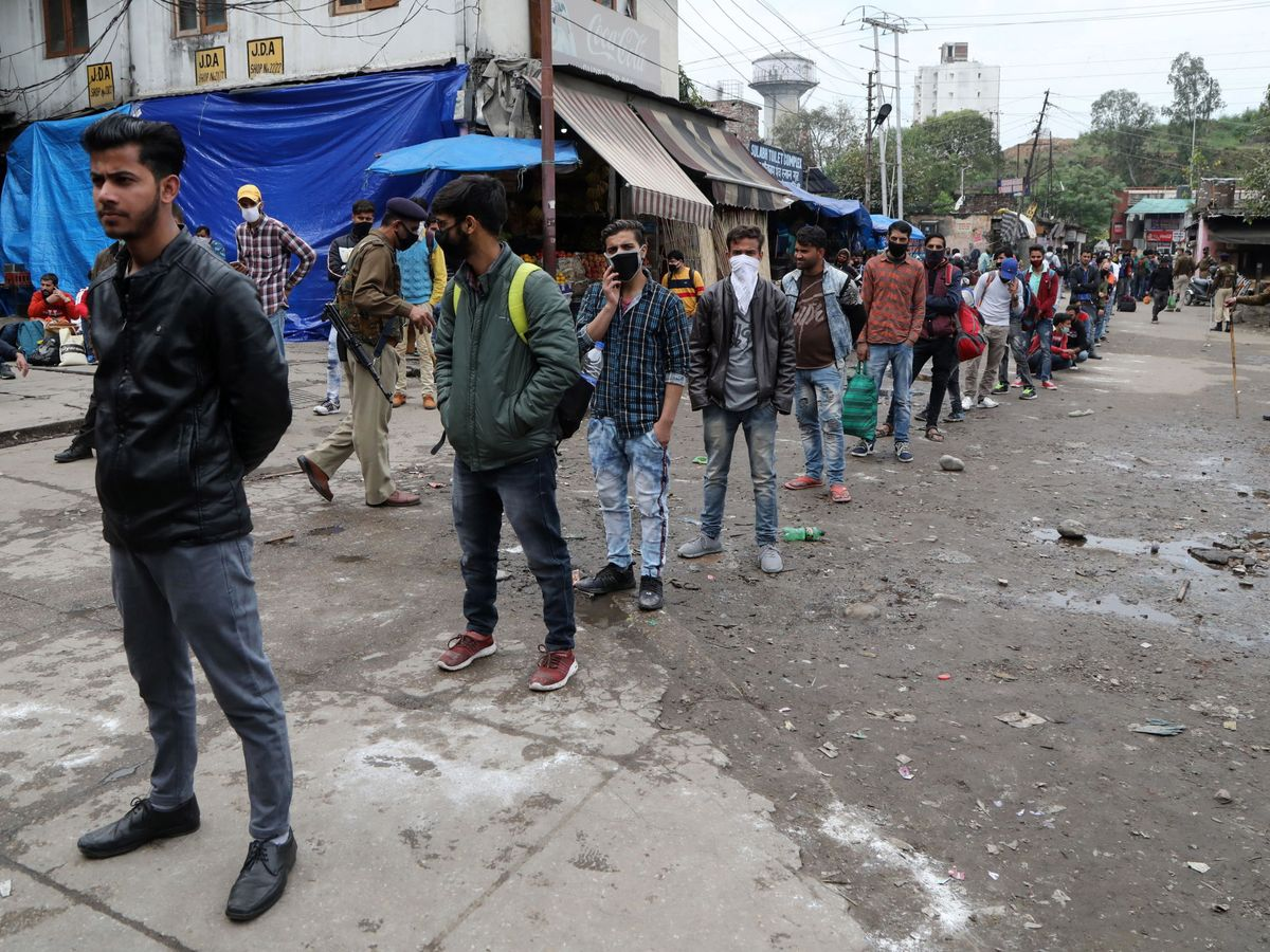 Foto: Varios pasajeros hacen cola esperando el autobús en la India. (EFE)