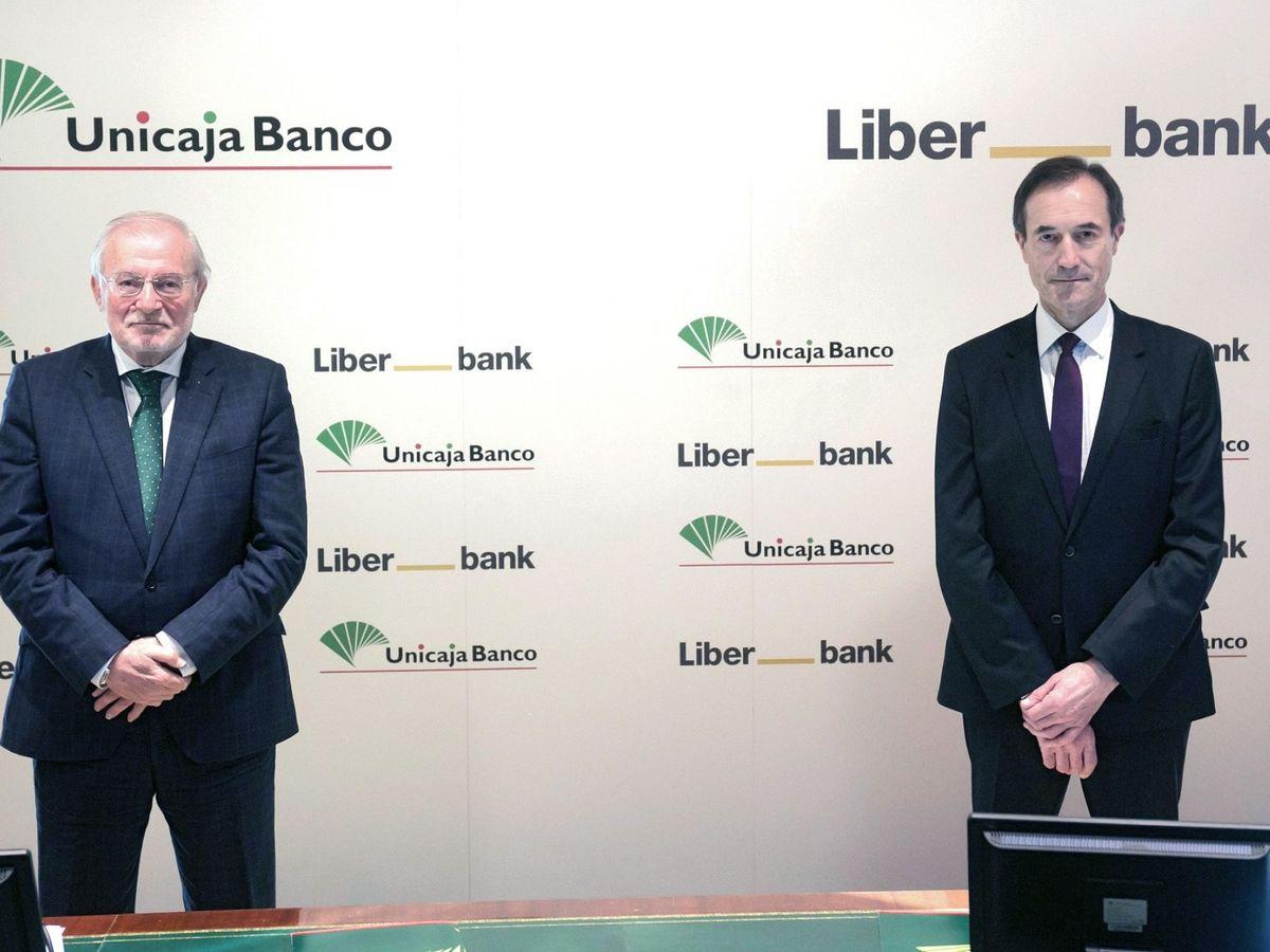 Foto: El presidente de Unicaja, Manuel Azuaga (i), junto con el consejero delegado de Liberbank, Manuel Menéndez. (EFE)