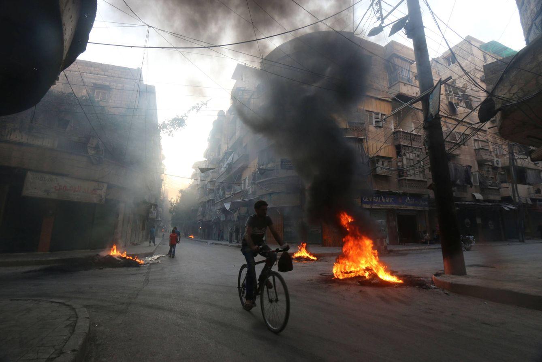 Foto: Un hombre pasa en bicicleta ante neumáticos ardiendo utilizados para ocultarse de la avicación siria en Alepo, el 1 de agosto de 2016 (Reuters).
