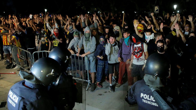 Manifestantes frente a los mossos en el Parlament de Catalunya. (Reuters)