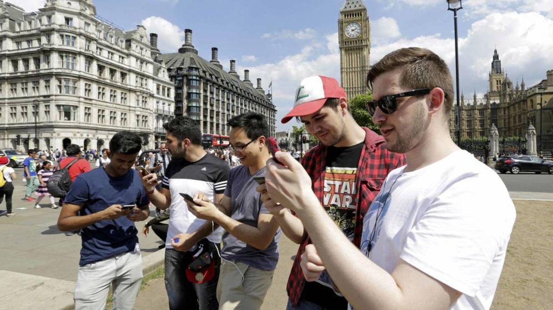Varios chicos utilizan su móvil frente al Big Ben de Londres (Reuters)