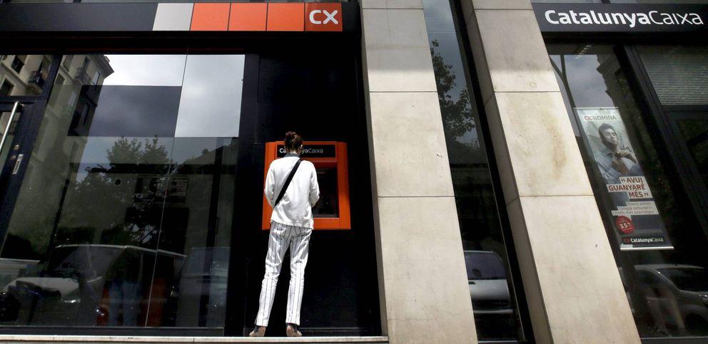 Foto: Una mujer utilizando un cajero automático de Catalunya Caixa en Barcelona. (EFE)