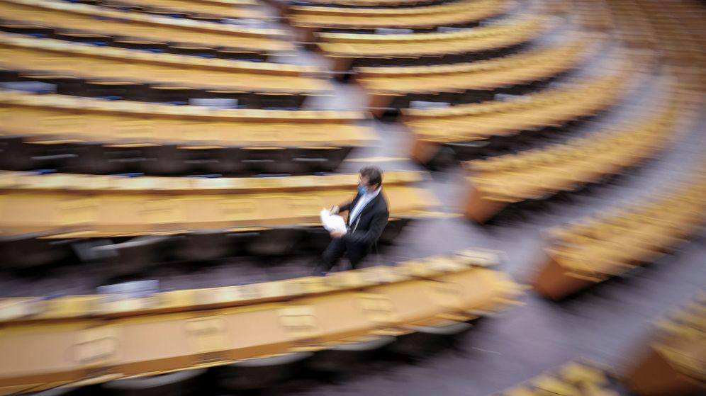 Foto: Un funcionario camina entre los escaños del Parlamento Europeo. (EFE)