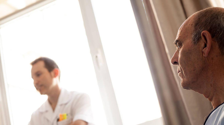 Foto: Eduardo, uno de los médicos de la unidad de paliativos de la Fundación Jiménez Díaz, visita a Jesús, un paciente con cáncer que ha decidido no tratarse. (Enrique Villarino)