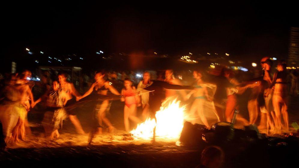 Foto: Un grupo de personas baila alrededor de una hoguera en la playa de San Juan de Alicante. (EFE)