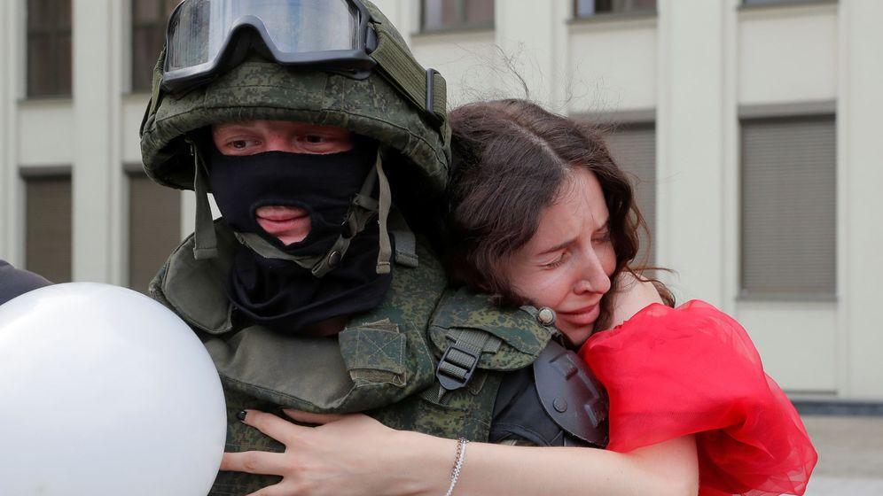Foto: Una opositora abrazando a un soldado a las puertas del Parlamento bielorruso en Minsk. (Reuters)