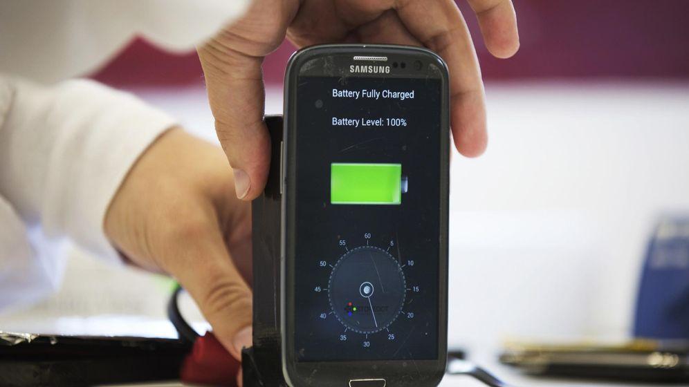 Foto: Un empleado desconecta un móvil de su base de carga. (Reuters)