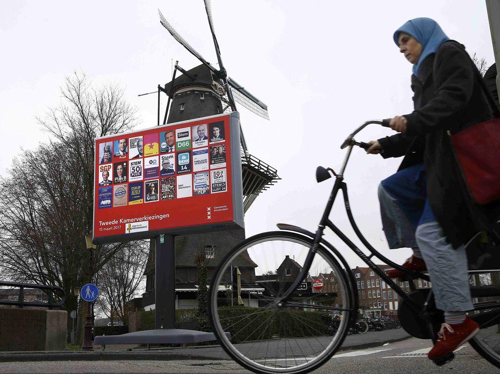 Foto: Una mujer ciclista pasa por delante de un cartel electoral y un molino en Ámsterdam, el 14 de marzo de 2017. (Reuters)