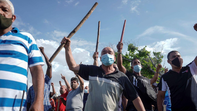 Manifestantes portando palos durante una marcha. (Reuters)