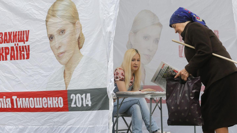 Una mujer recoge propaganda electoral de la candidatura de Timoshenko. (Efe)