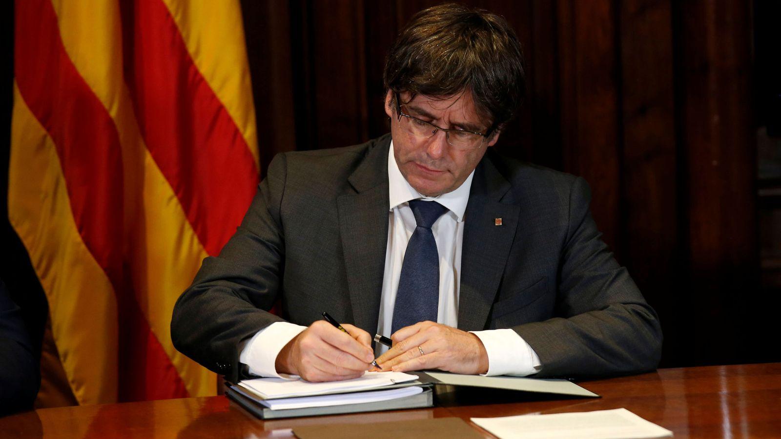 Foto: El presidente de Cataluña, Carles Puigdemont, firma el decreto de convocatoria del referéndum. (Reuters)