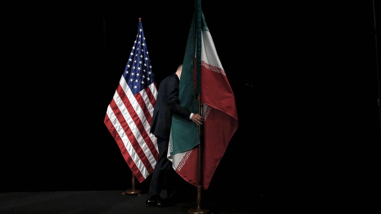 Un trabajador retira una bandera de Irán tras una cumbre sobre el acuerdo nuclear, en Viena, el 14 de julio de 2015. (Reuters)