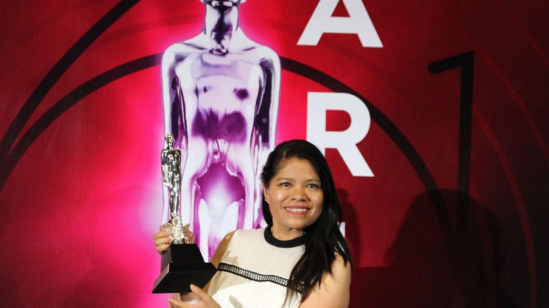 La actriz Marcelina Bautista, en nombre de Alfonso Cuaron, posa con el premio a mejor dirección en la alfombra roja durante la 61 edición de los Premios Ariel que otorga la Academia Mexicana