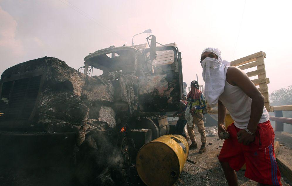 Foto: Manifestantes se enfrentan con miembros de la Policía Nacional Bolivariana, junto a un camión que transportaba ayuda humanitaria y fue quemado en la frontera con Colombia. (EFE)