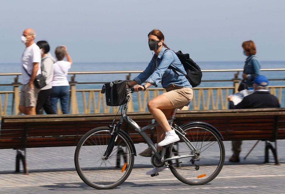 Foto: Una mujer pasea en bicicleta cubierta con una mascarilla por San Sebastián. (EFE)