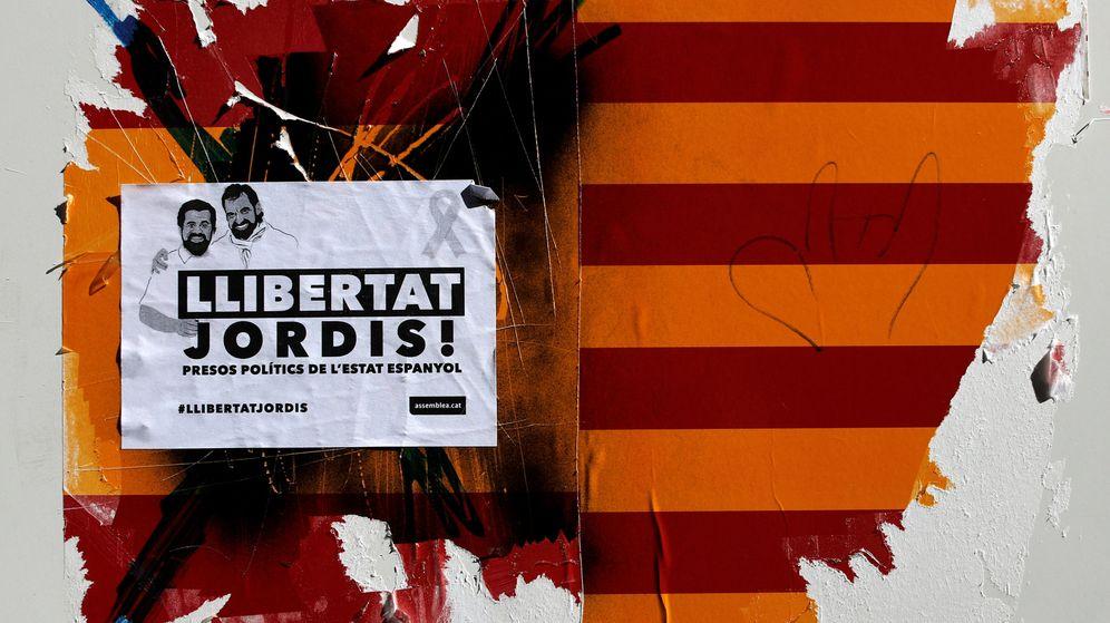 Foto: Un cartel que exige la libertad de los exlíderes de la ANC y Òmnium Cultural sobre unas banderas desgarradas de España y Cataluña. (Reuters)