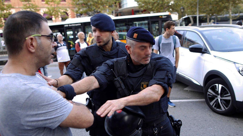 Un manifestante es deslojado de la calzada en las inmediaciones de la Plaza de España de Barcelona. (EFE)