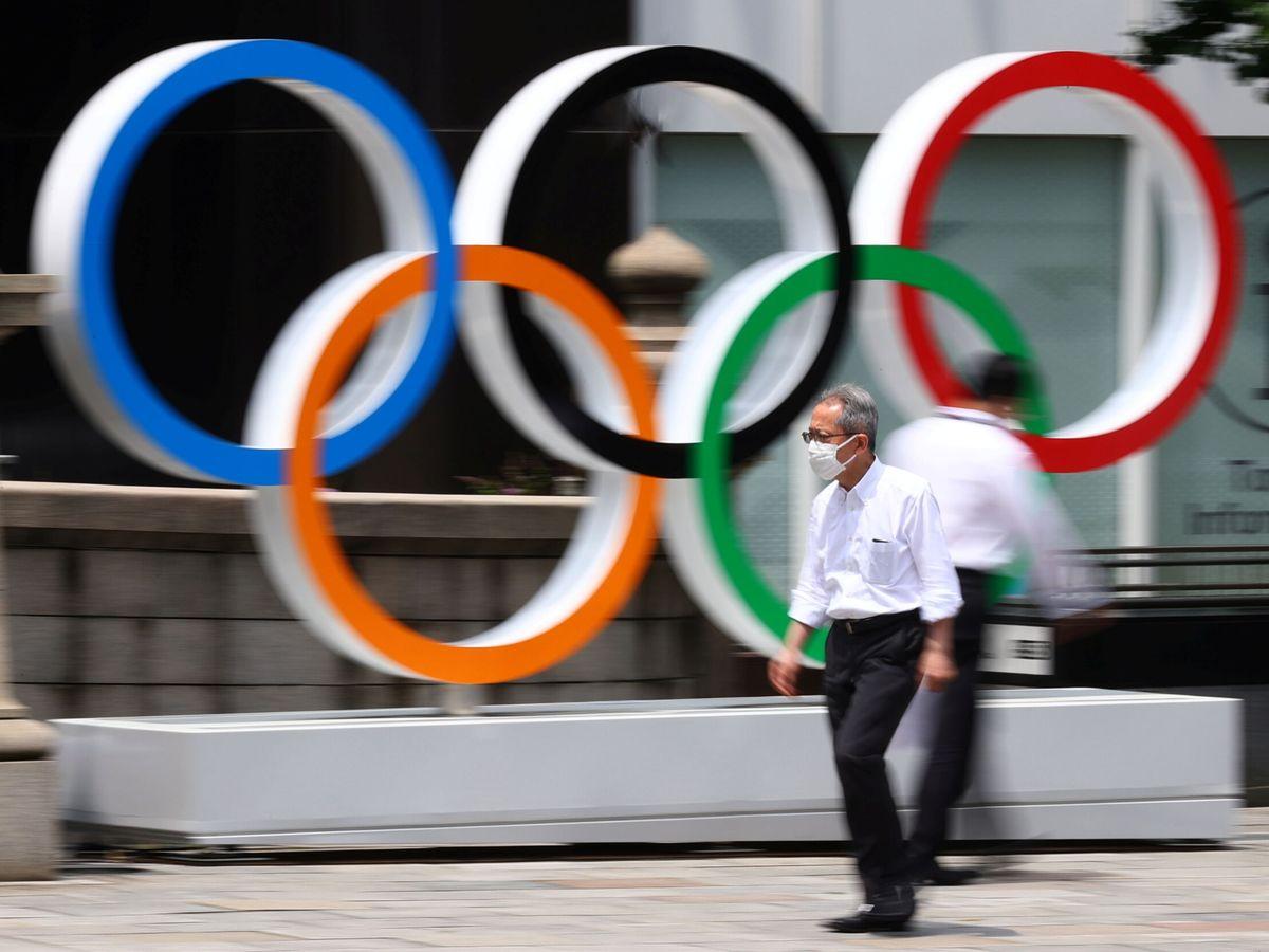 Foto: Un hombre con mascarilla pasa por delante de los anillos olímpicos de Tokio. (Reuters)