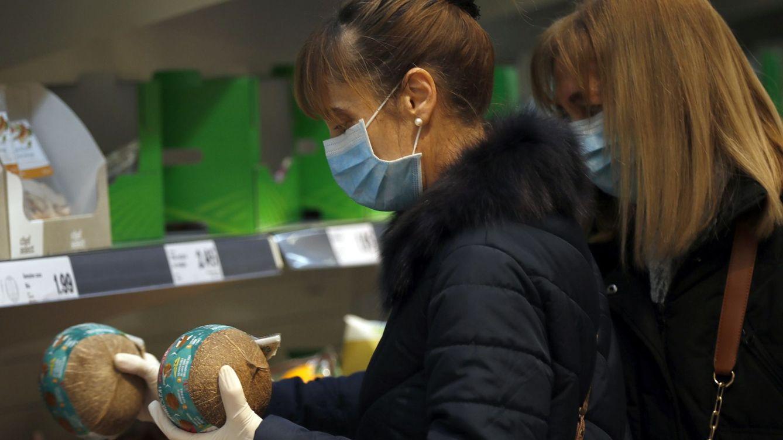 Foto: Dos mujeres con mascarilla y guantes se abastecen en un supermercado en Bilbao. (EFE)
