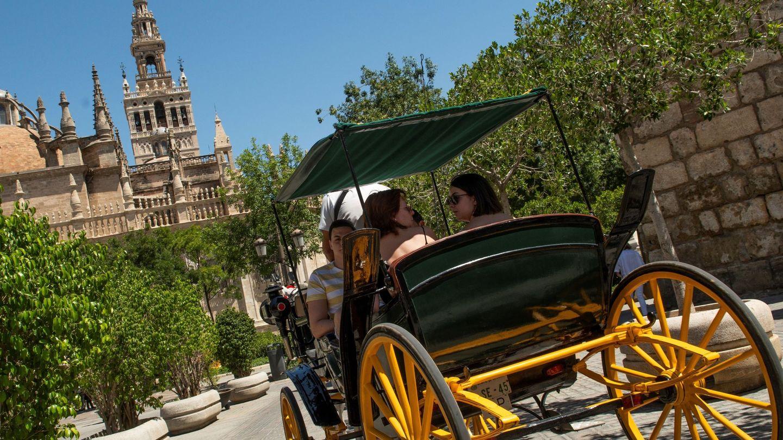 Turistas pasean por Sevilla en coche de caballos. (EFE)