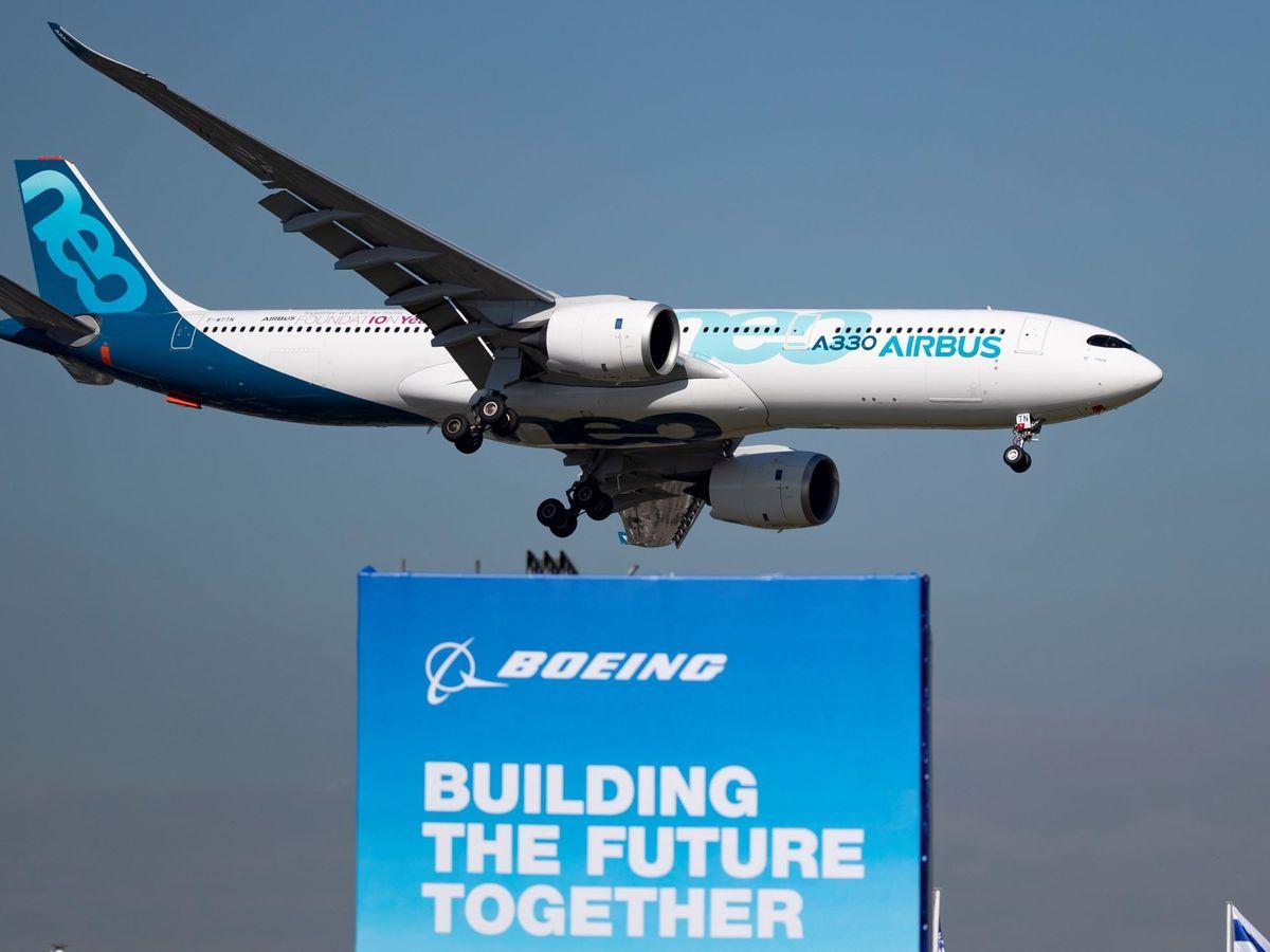 Foto: Un avión Airbus A330 Neo sobrevuela un cartel publicitario de Boeing. (EFE)