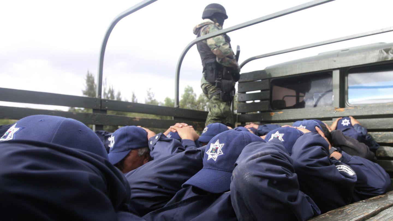 Un soldado custodia a 24 policías arrestados en Tarimbaro (Michoacán) por vínculos con el narcotráfico (Reuters).