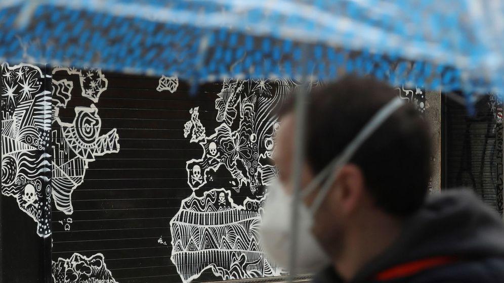 Foto: Un hombre con mascarilla pasa ante un local cerrado, en Madrid. (EFE)