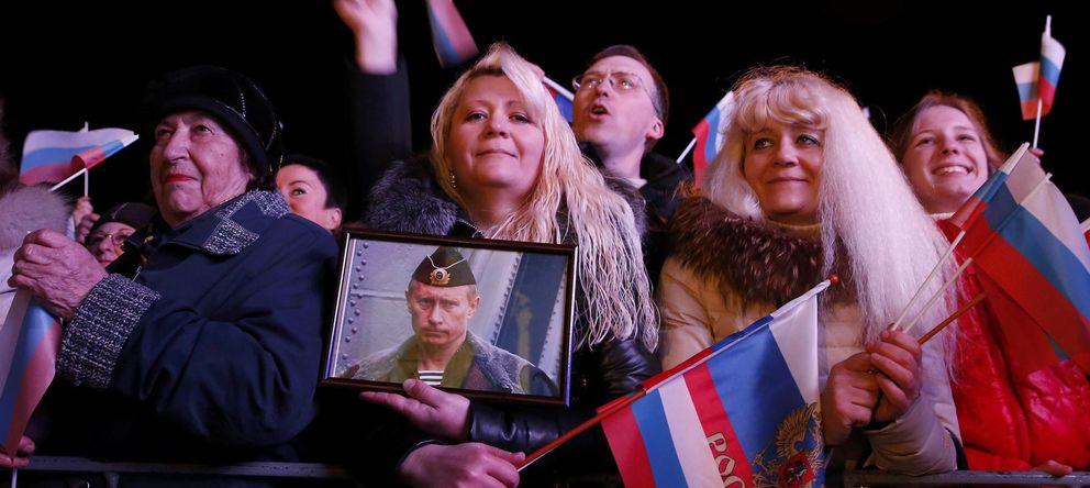 Foto: Una mujer sostiene un retrato de Putin en la ciudad de Sebastopol, en Crimea (Reuters).