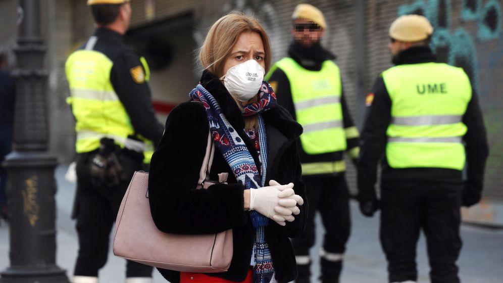 Foto: Una mujer camina con una mascarilla junto a miembros de la UME en la calle Carretas en Madrid. (EFE)