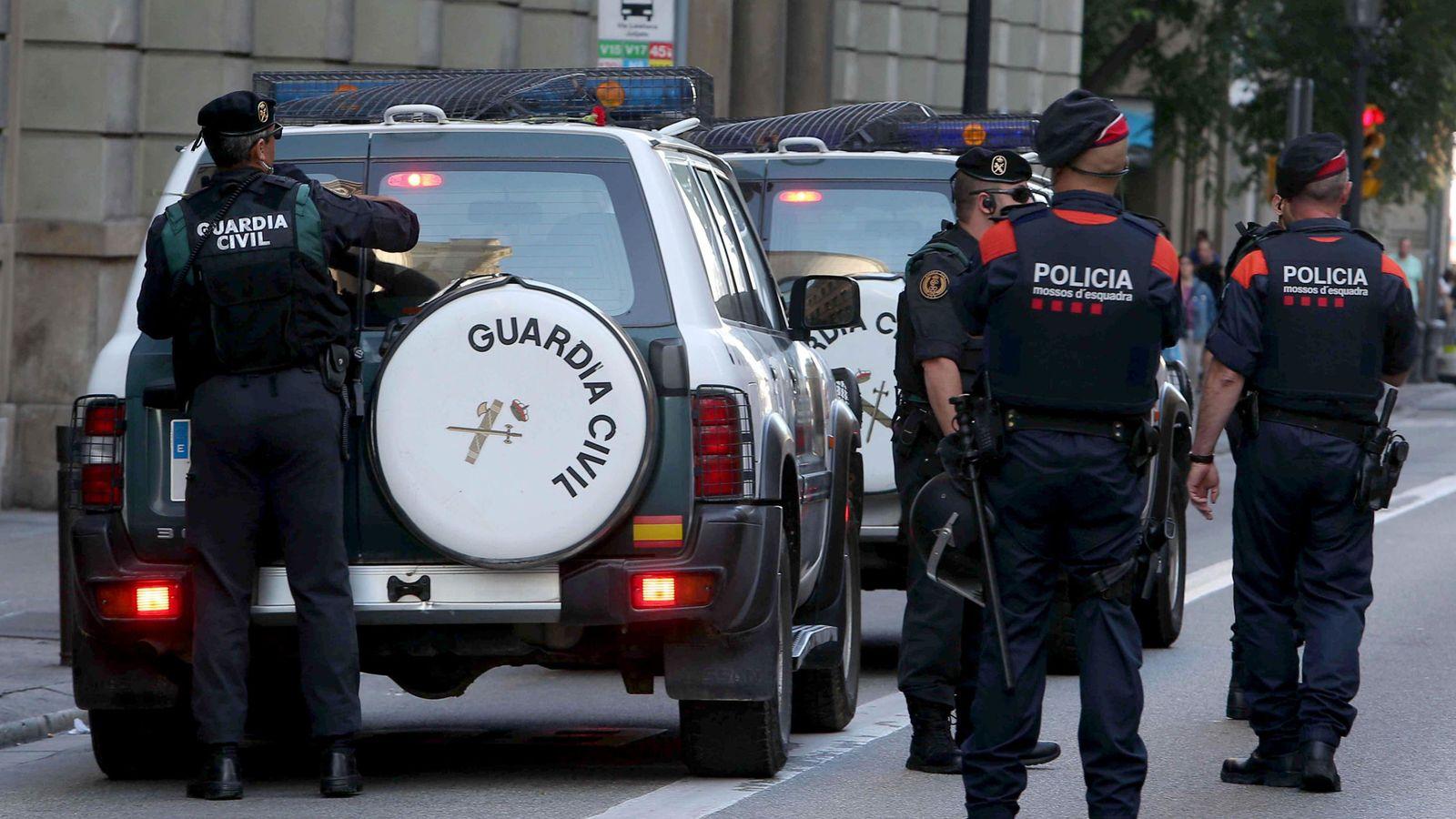 Foto: Un coche de la Guardia Civil frente a un grupo de Mossos. (EFE)
