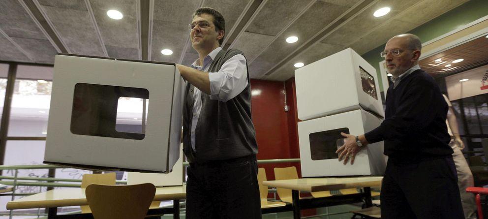 Foto: Dos voluntarios, colocando urnas en un colegio del centro de Barcelona. (Efe)