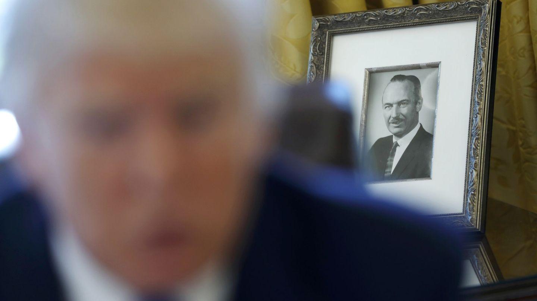 Donald Trump da una entrevista con el retrato de su padre, Fred, de fondo. (Reuters)