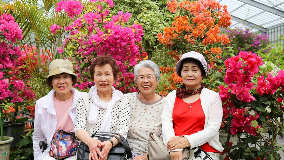 Foto: Unas ancianas okinawenses, rodeadas de flores. (iStock)