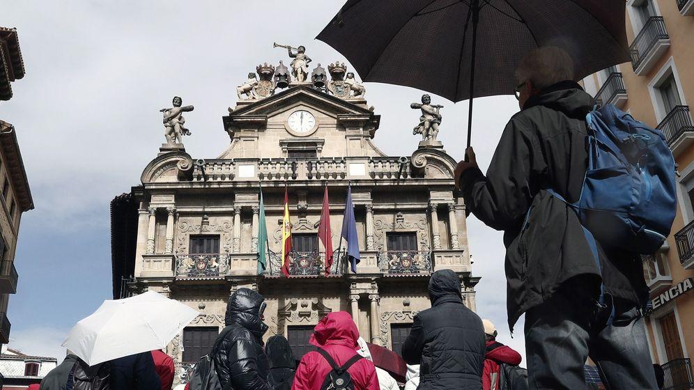 Foto:  Un grupo de turistas se protegen con sus paraguas de la lluvia junto al Ayuntamiento de Pamplona este jueves. (EFE)