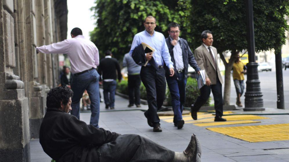 Foto: Un hombre pide en la calle de una zona financiera. (EFE)