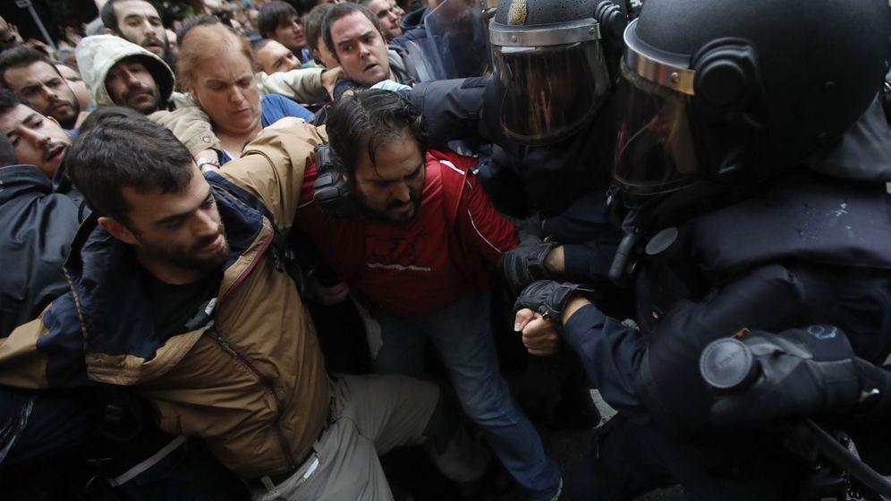 Foto: Agentes antidisturbios de la Policía Nacional forman un cordón de seguridad ante un colegio el 1-O. (EFE)