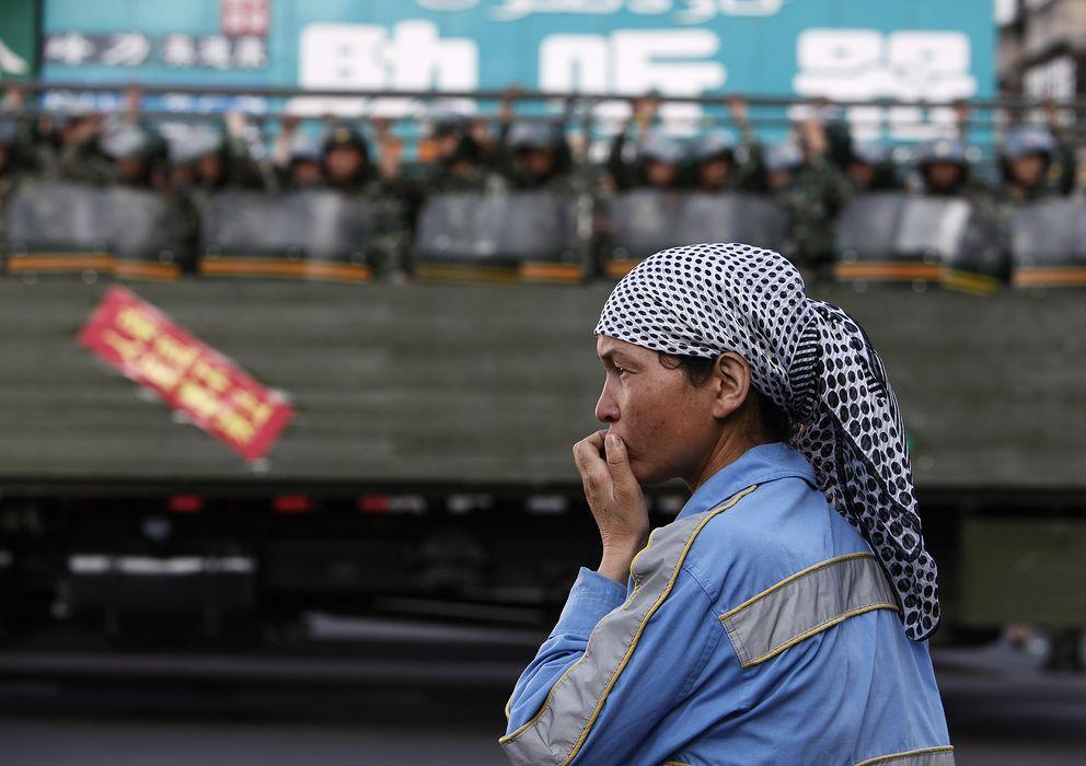 Foto: Una mujer uigur ante un camión de la policía paramilitar china en Urumqi, capital de la provincia de Xinjiang (Reuters)