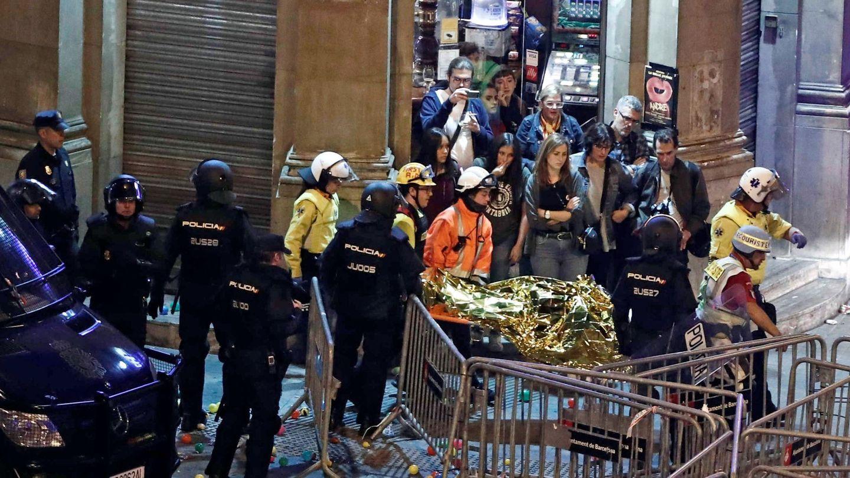 Varios sanitarios transportan a un herido en los enfentamientos de la Via Laietana. (EFE)