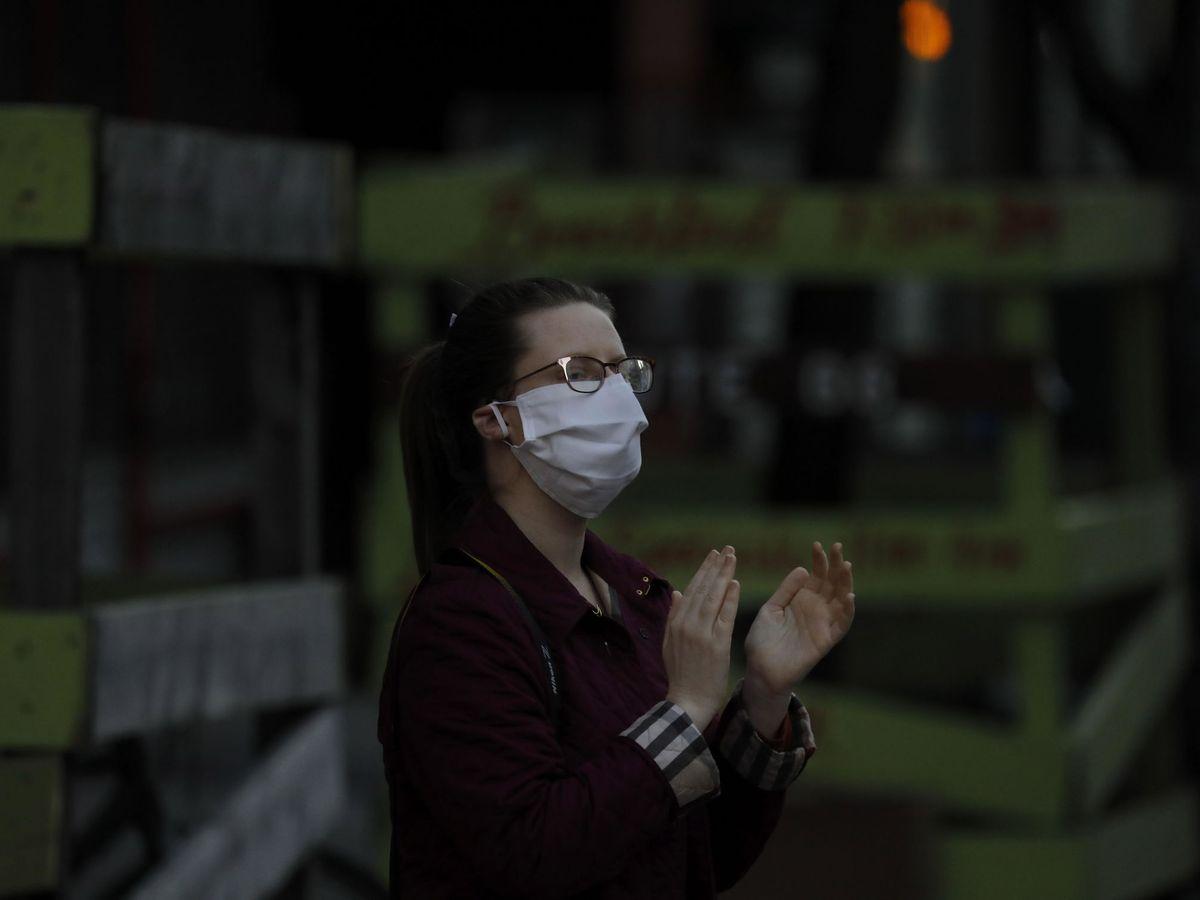 Foto: Una mujer aplaude en apoyo a los trabajadores sanitarios de Nueva York (EFE)