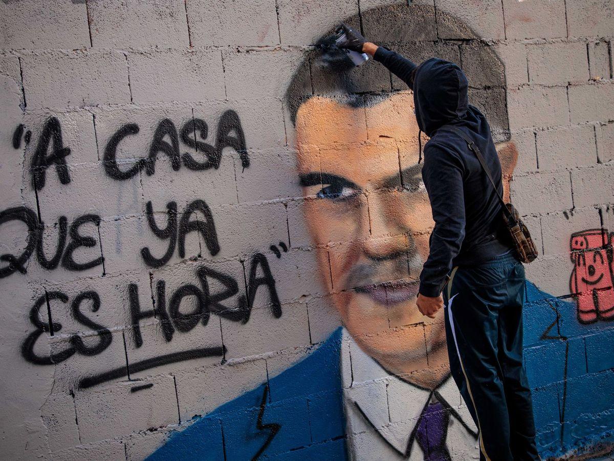 Foto: El artista urbano J. Warx realiza un grafiti en Valencia en relación a la pandemia de covid-19. (EFE)